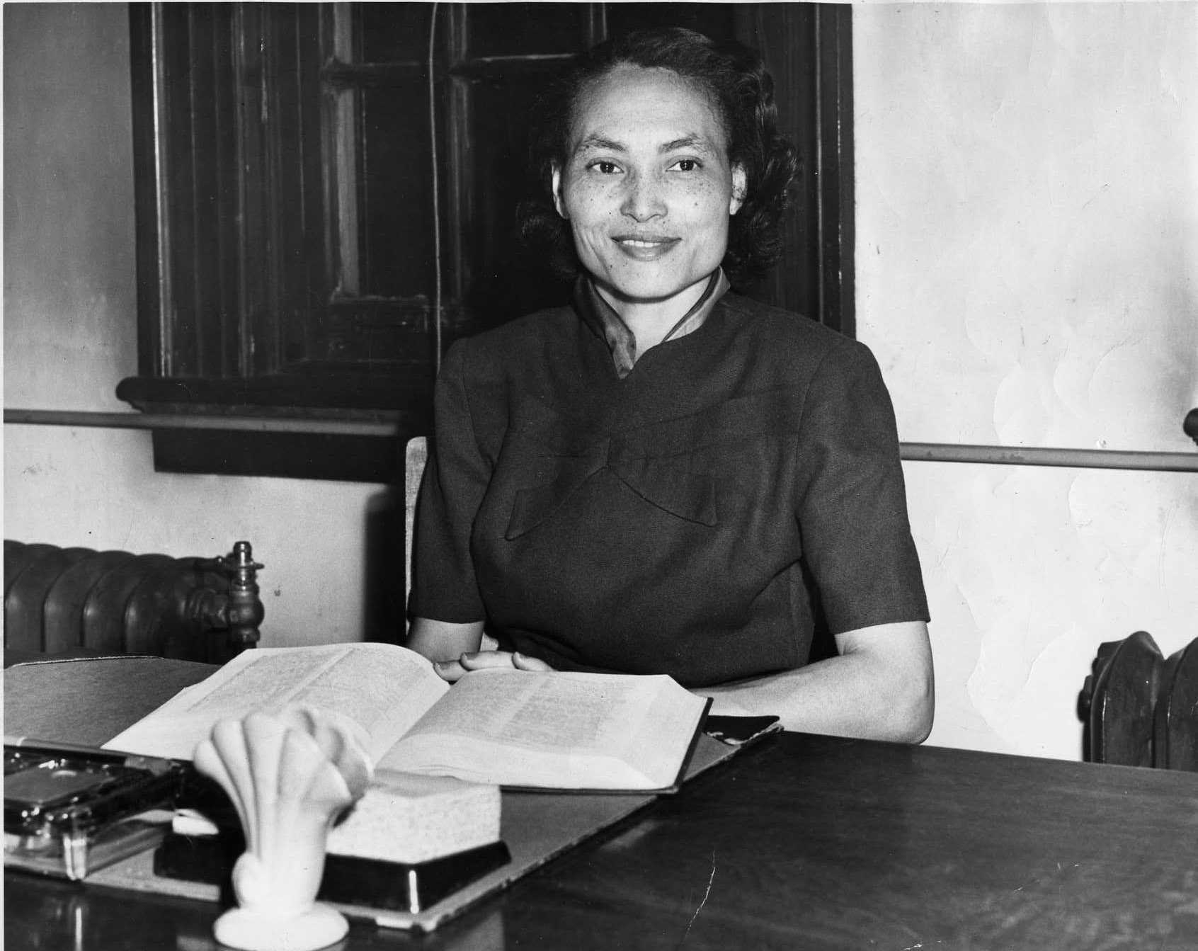 Annie McPheeters sits at a desk with an open book in front of her.