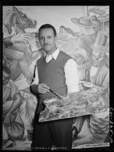 Hale Aspacio Woodruff stands in front of a mural with a paint brush in his hand.