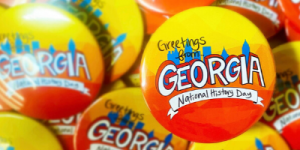 "National History Day Georgia buttons which feature a drawing of the Atlanta skyline and the text, ""Greetings from Georgia."""