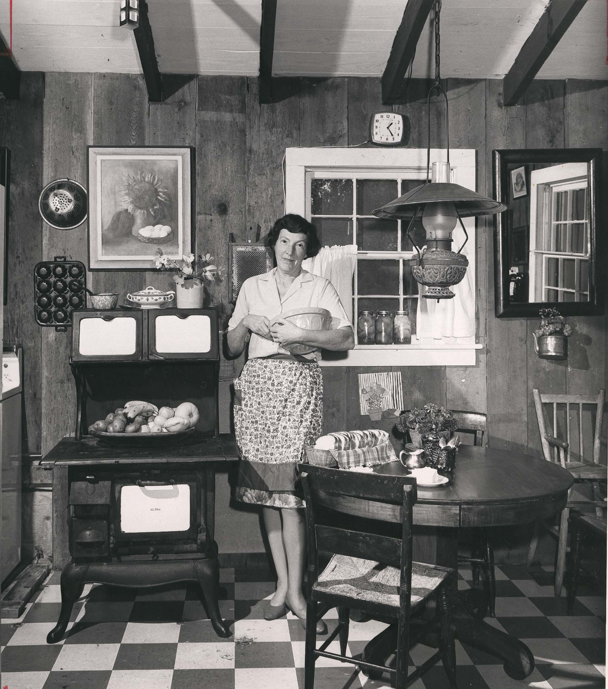 Celestine Sibley stands in a kitchen with a bowl in her hand.