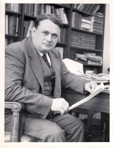 Ralph McGill sits at a desk, holding a piece of paper.