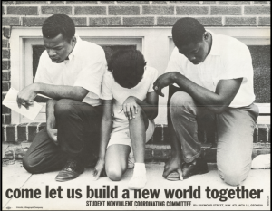 """Three people kneel with the words """"come let us build a new world together"""" typed underneath."""